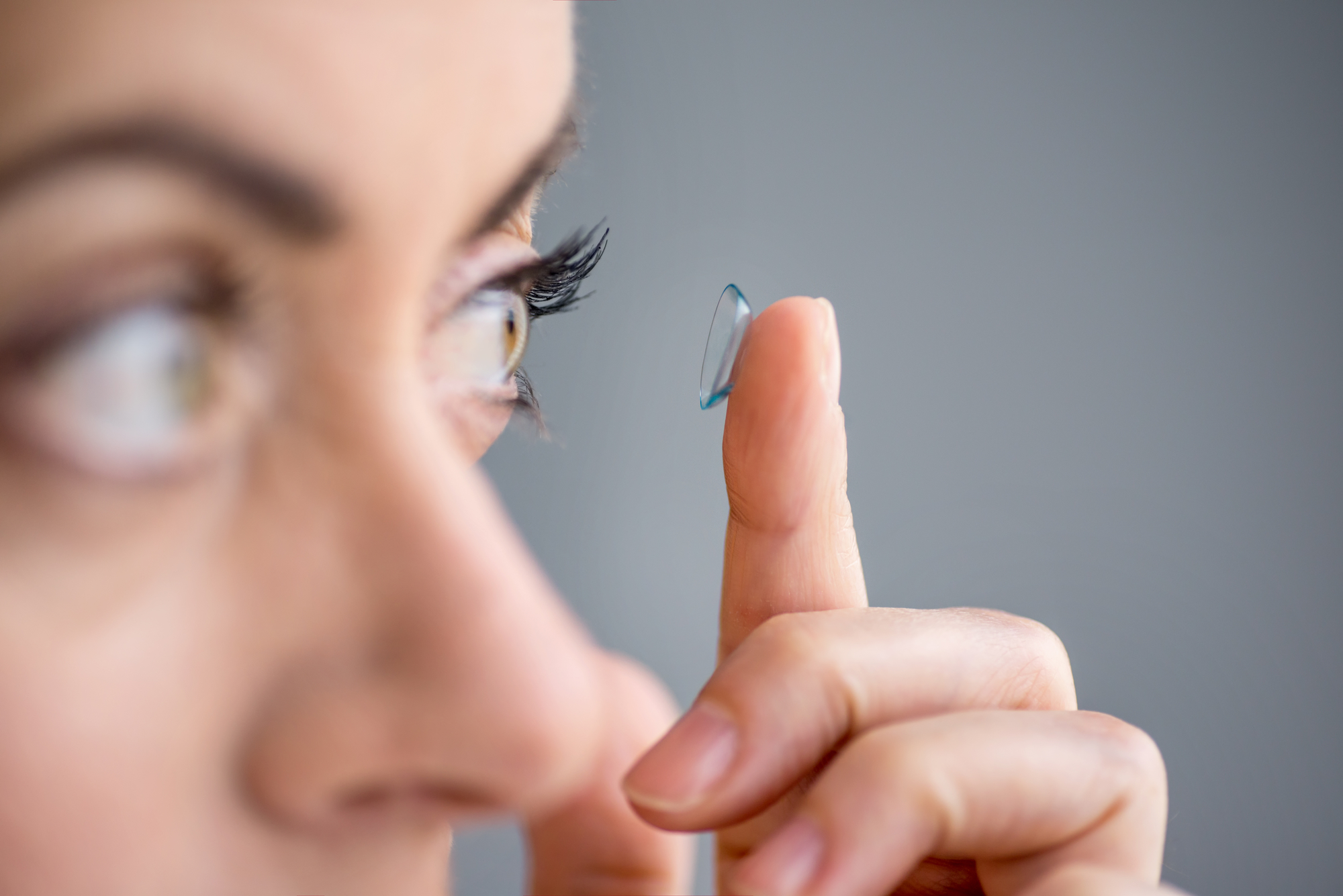 woman in her forties inserting contact lenses